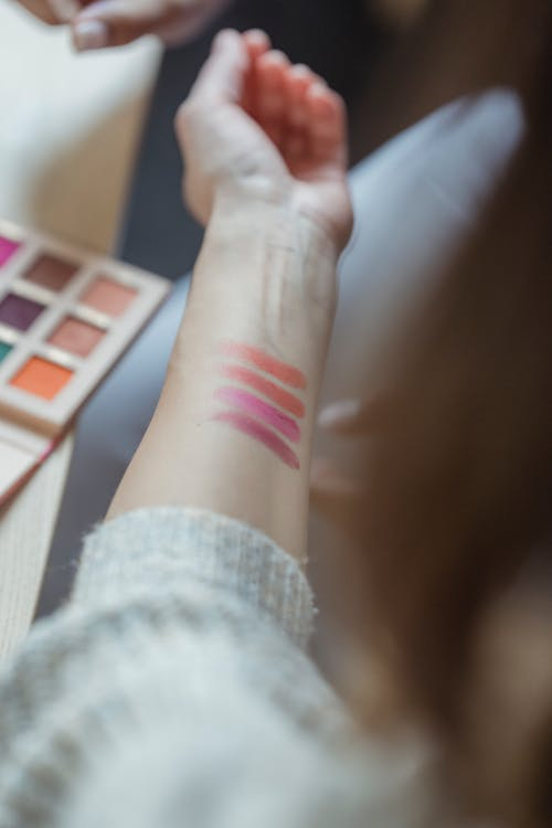 Crop anonymous professional female makeup artist with cosmetic product swatches on arm skin sitting in beauty salon