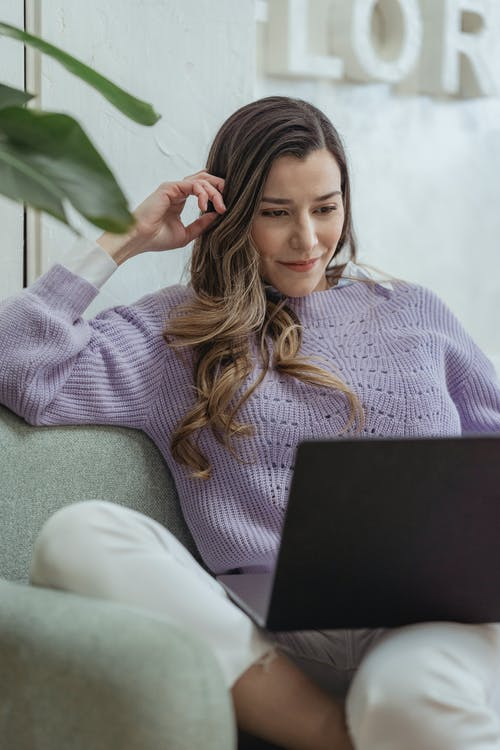 Young content female wearing casual clothes browsing netbook and touching hair while sitting on cozy sofa