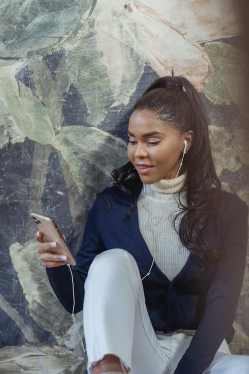 Content black woman using smartphone and listening to music
