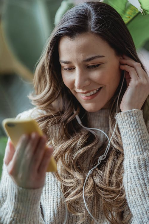 Young content female in casual sweater browsing modern mobile phone and listening to good music via earphones in living room