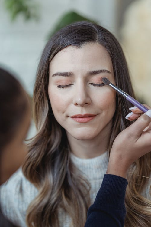 Makeup artist with brush applying eyeshadows on glad female customer in light beauty studio