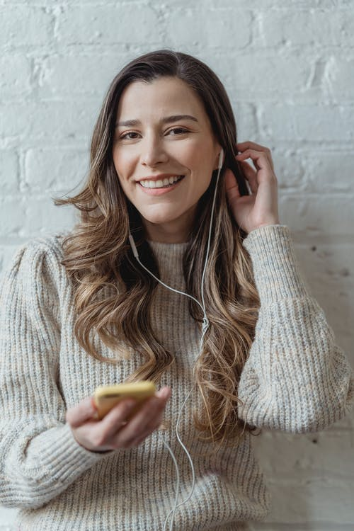 Young content female in sweater and earphones browsing mobile phone and looking at camera while standing against brick wall and touching hair