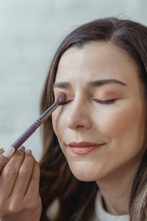 Crop visagiste applying eyeshadows on female model