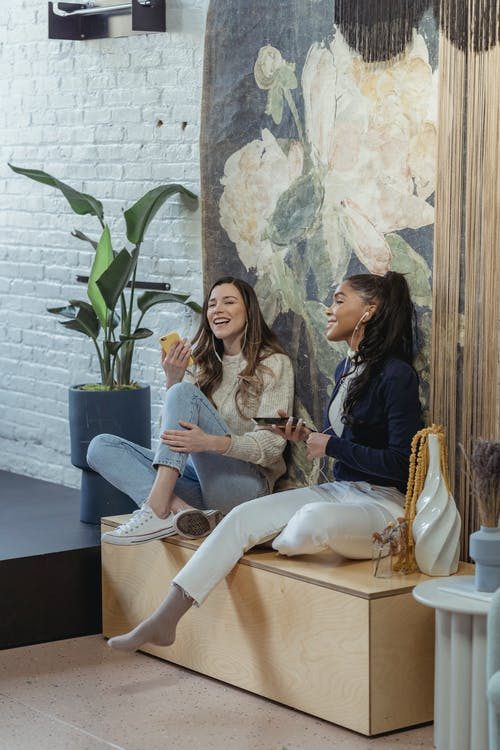 Full body joyful multiracial female friends in casual clothes using smartphones and listening to good music via earphones in modern living room
