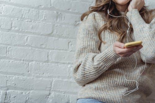 Crop lady using smartphone and enjoying music in earphones
