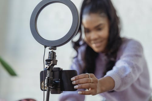 Cheerful young African American female blogger in stylish sweater smiling while setting up camera of smartphone attached to tripod with ring light before recording vlog