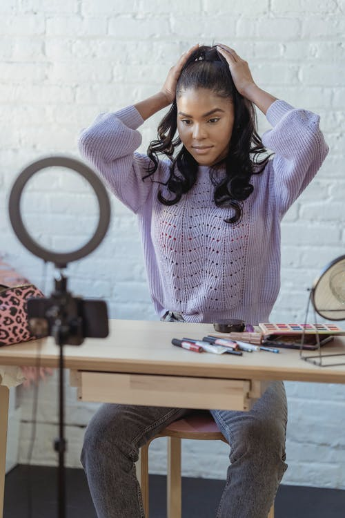 Stylish young African American female influencer in sweater adjusting long dark hair while sitting at wooden table before recording makeup tutorial video on smartphone