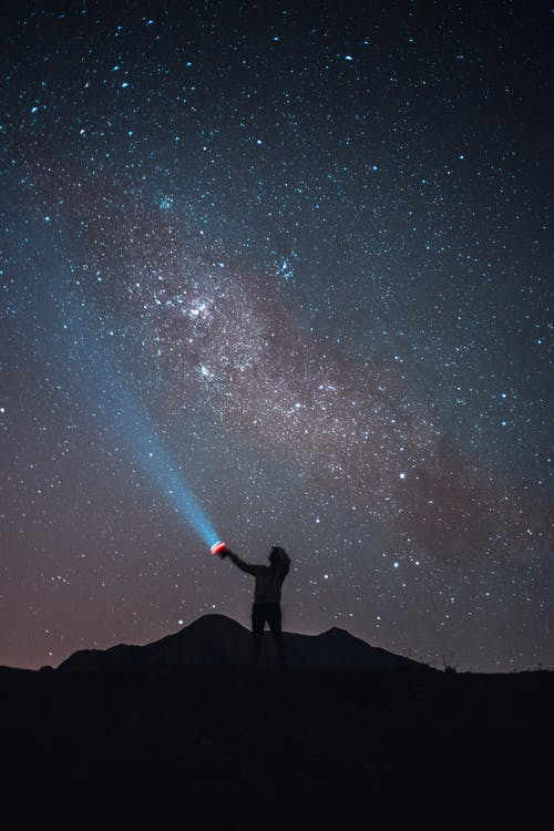 Silhouette of anonymous tourist standing on cliff and signaling with flashlight against cloudless starry night sky