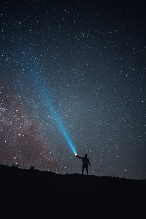 Breathtaking view of unrecognizable hiker and blue beam against majestic scenery of randomly scattered stars on dark night sky