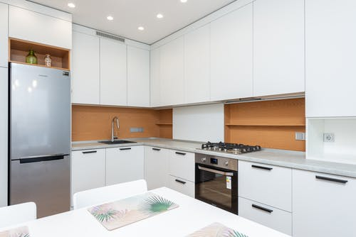 Contemporary kitchen with gas stove and oven against table with placemats and refrigerator reflecting shiny lamps in house