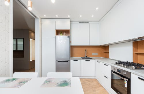 Modern kitchen interior with fridge and cabinets against table with placemats under lamps in house