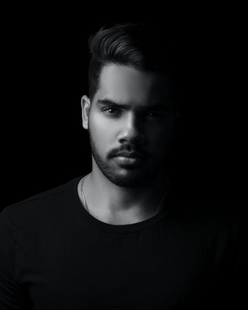 Focused young stylish man looking at camera in dark studio