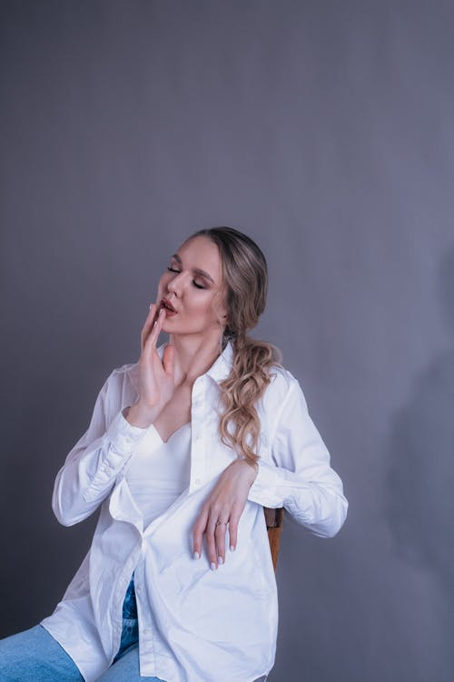 Thoughtful young woman in shirt sitting on chair with closed eyes and hand on mouth on gray background in bright studio