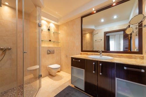 Shower room against toilet bowl and cabinet with washbasin under mirrors illuminated by shiny lamps in modern house