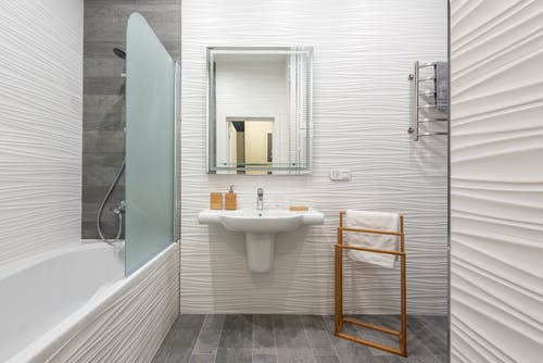 Contemporary bathroom interior with bathtub and washstand with toiletry products under mirror in light house