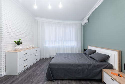 Contemporary bedroom interior with bed against table and chest of drawers on parquet under shiny light bulbs
