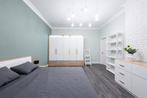 Bed with pillows and crumpled cover against closet and commode illuminated by light bulbs in modern house