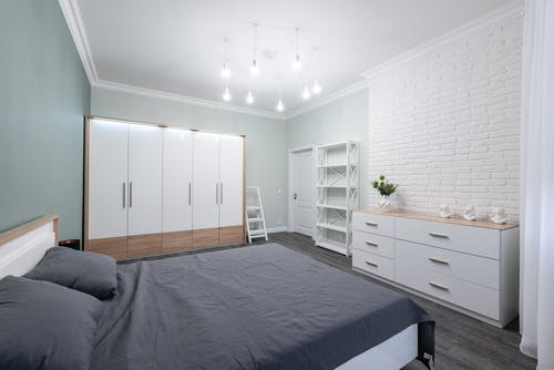 Interior of modern bedroom with minimalist white furniture and comfy bed in apartment