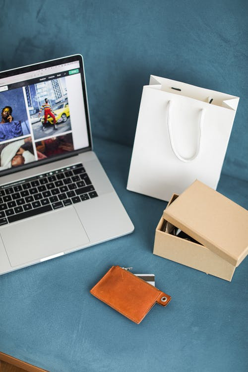 A Macbook Beside An Online Purchased Product In Box
