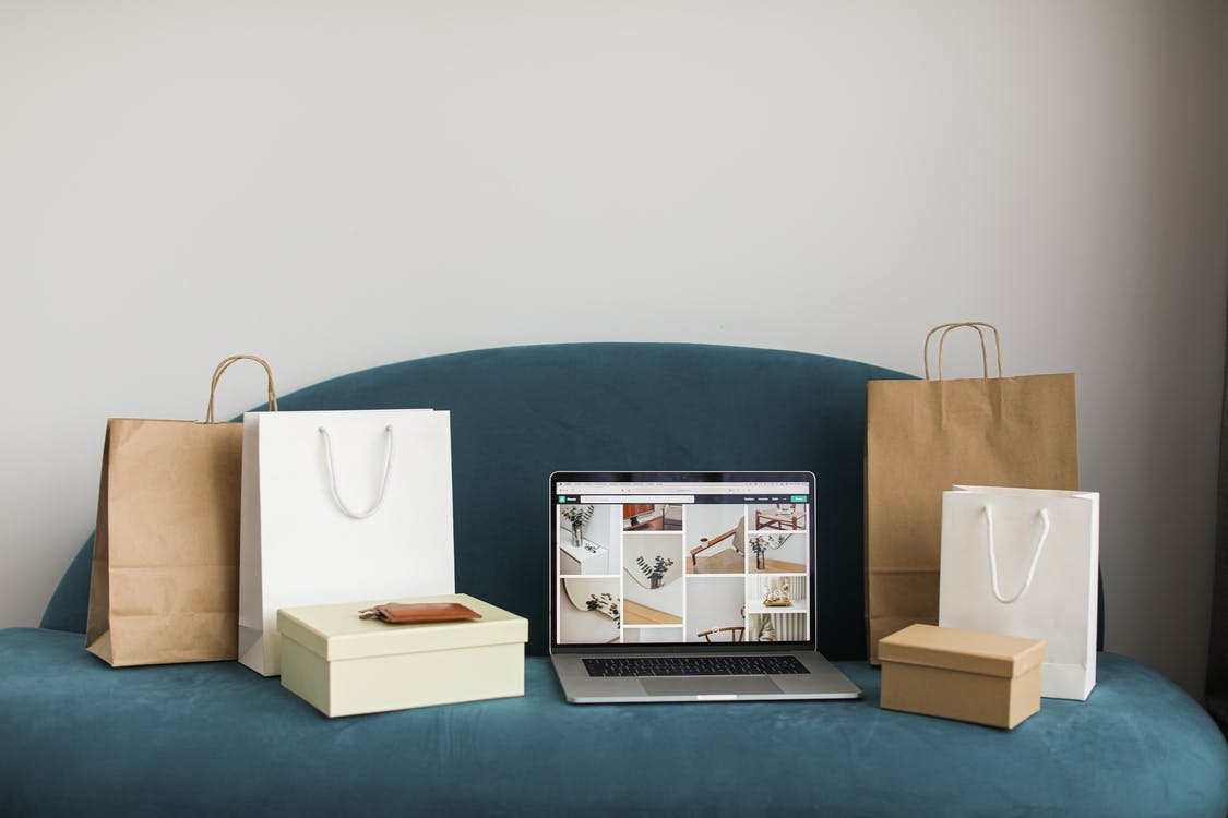 Macbook Pro With Shopping Bags and Boxes On Blue Couch