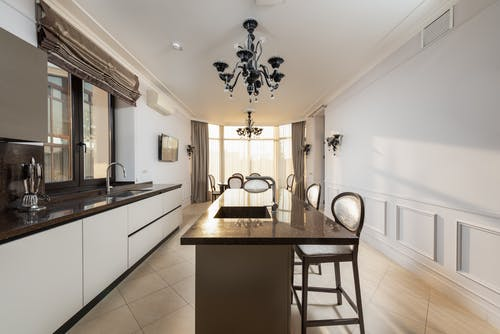 Chairs at table with sink near white cupboards and counter with supplies in spacious modern kitchen with window at home