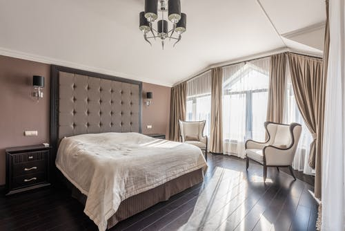 Comfortable bed with white bedclothes placed at wall with lamps between bedside tables in modern bedroom with armchairs and window