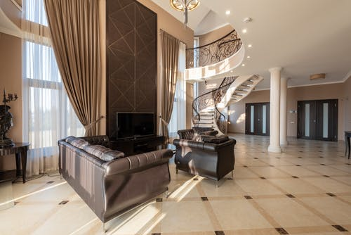 Soft leather black couches on tiled floor near window with curtains in modern stylish house with stairway and doors near columns