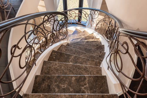 From above of spiral stairway with marble steps and metal railings with decorative elements located in modern light building with window