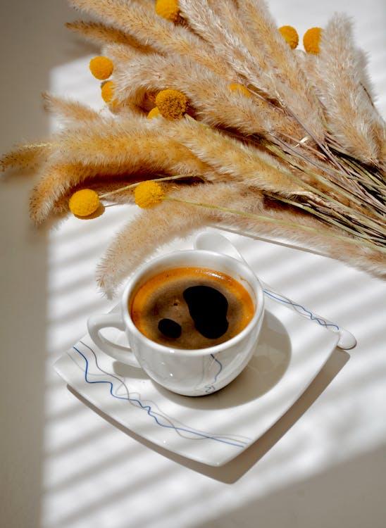 Coffee cup near craspedia flowers