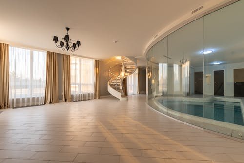 Swimming pool with clear water behind glass wall placed in modern hall with stairway and windows with curtains in contemporary house