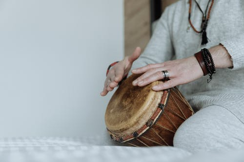 Close Up Photo of Person Playing Djembe