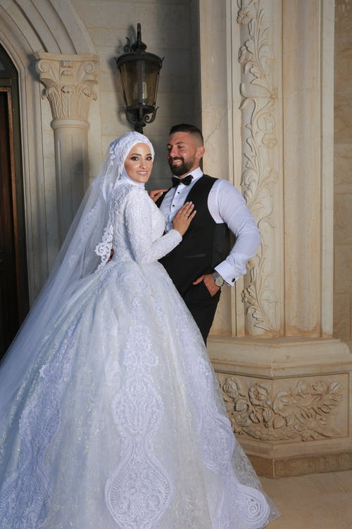 Groom Standing Beside A Bride in White Wedding Dress