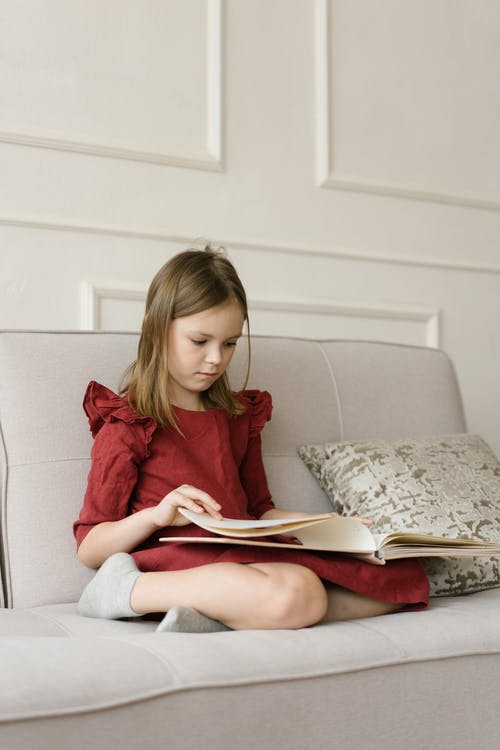 Girl in Red Long Sleeve Shirt Reading Book