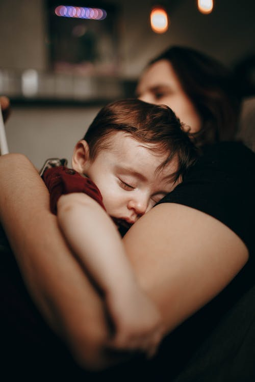 Little son sleeping in arms of anonymous mother