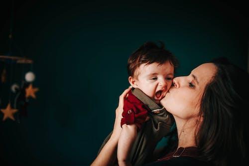 Loving mother kissing cute son