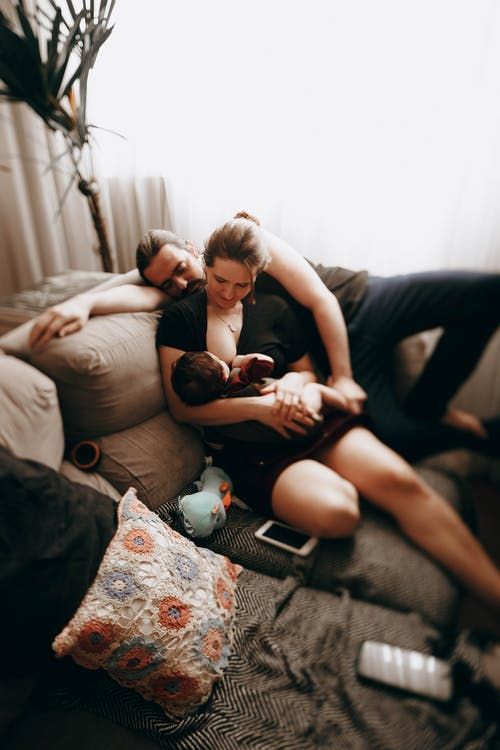Caring mother breastfeeding little baby while sitting on comfortable sofa near father while spending time together at home in living room