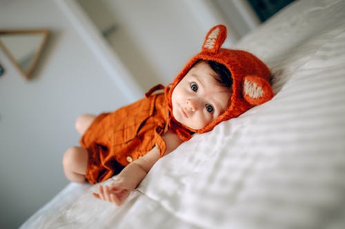 Cute baby in costume lying on bed