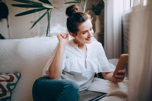 Smiling female in casual clothes sitting on comfortable sofa in light room and browsing smartphone