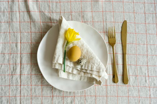 Yellow Fruit on White Ceramic Plate Beside Brown Wooden Fork and Knife