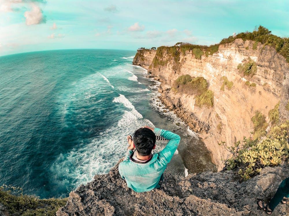 Man Wearing Blue Long Sleeve Top On Top Of Mountain Near Body Of Water