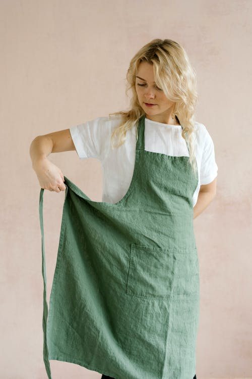 Woman putting on apron for housework