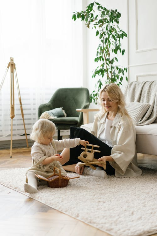 Cute little girl playing toys with mother