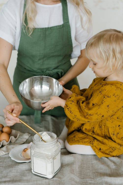 High angle of little daughter sitting on table with stainless bowl helping mother in making dough