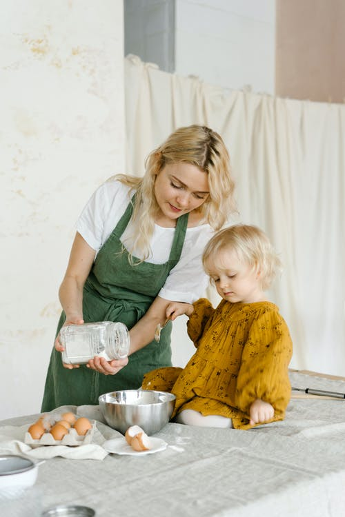 Woman cooking near little cute girl on table