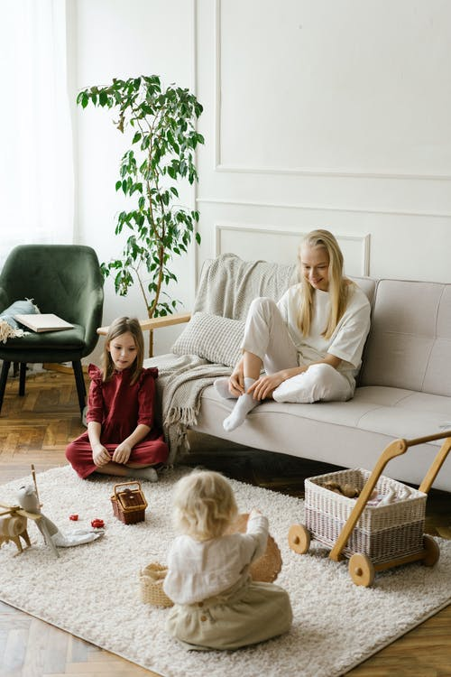 Mother watching children playing with toys on soft carpet