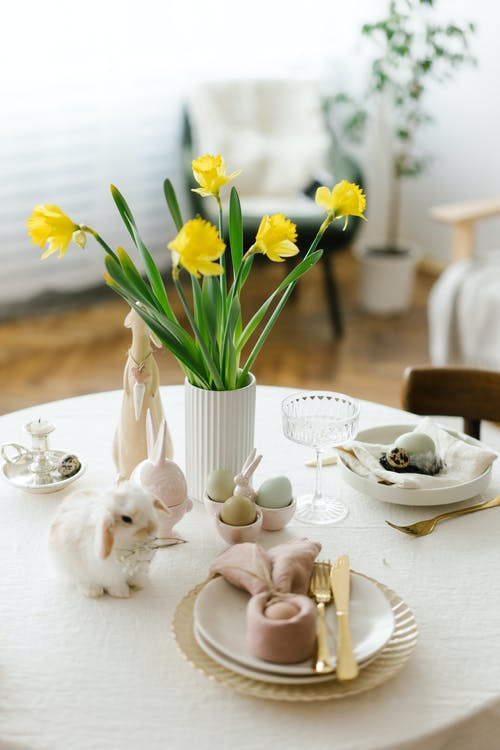 From above of festive table with Easter eggs and bouquet of yellow daffodil flowers in light room in daytime