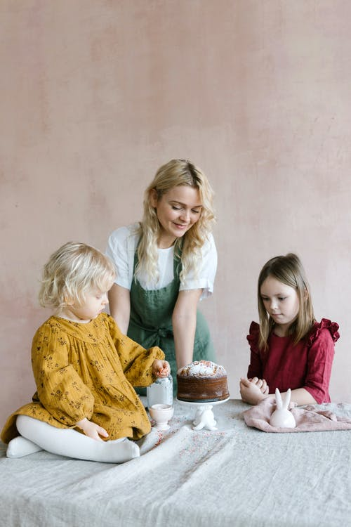 Mother with daughters preparing Easter cake