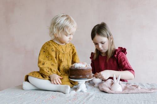 Small girls in stylish clothes preparing tasty Easter cake in light room in daytime