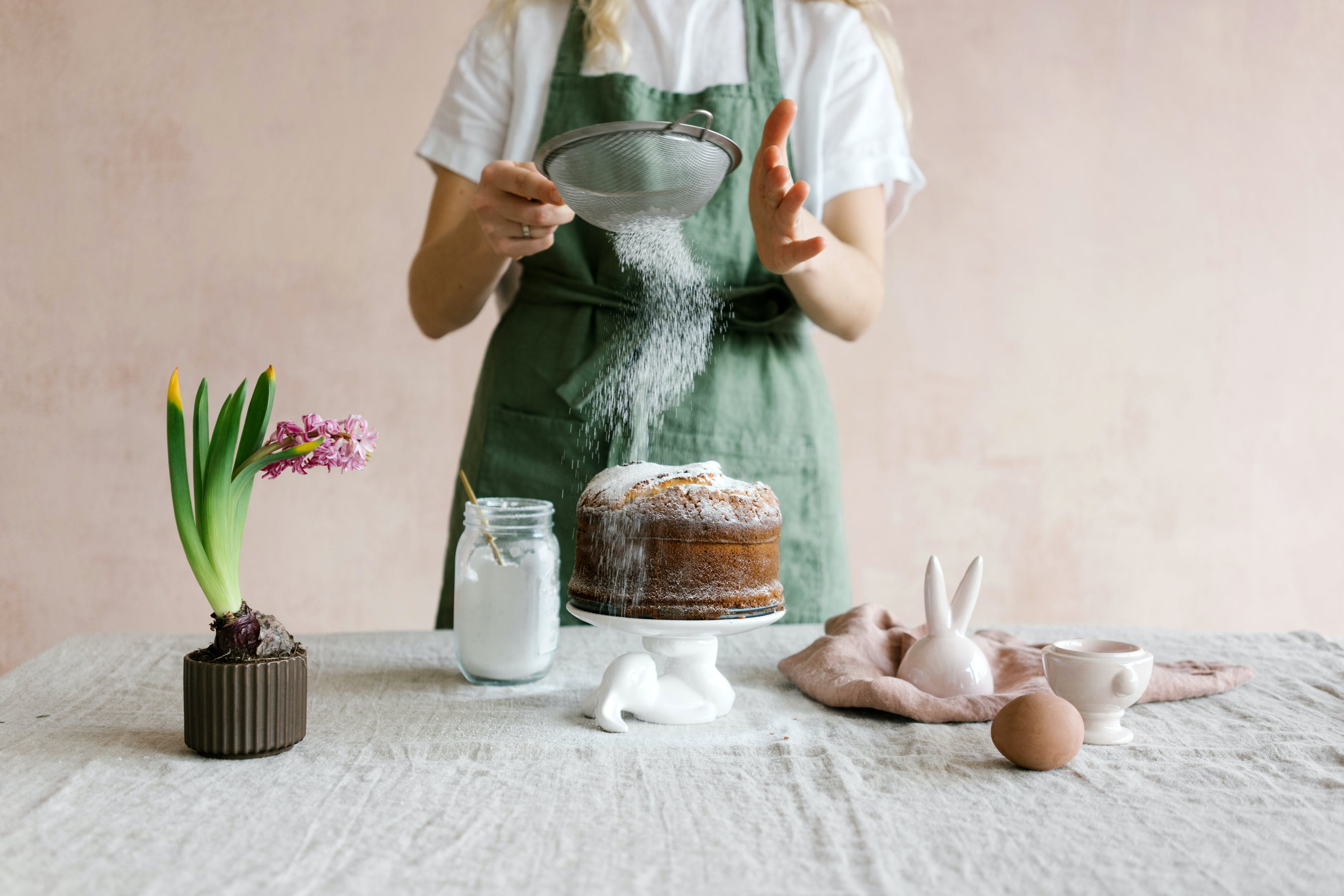 Anonymous female serving cake with icing sugar