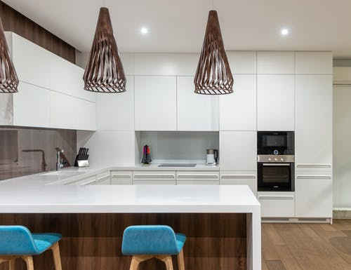 Turquoise chairs at counter with white cupboards and modern kitchenware in spacious light kitchen with hanging lamps in contemporary apartment